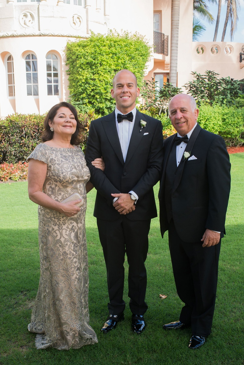 Mother of groom in short sleeve gown with father of bride in tuxedo groom in bow tie