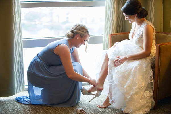 Maid of honor helping bride into sparkling heel