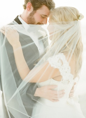 Bride in a Monique Lhuillier gown with a lace bodice and veil embraces groom in a black tuxedo.