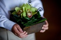 Wood box with jungle leaves and green orchids