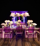 Round-back ghost chairs in purple at head reception table