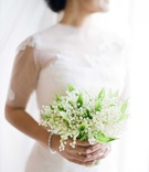 Bride in Vera Wang wedding dress holding small bouquet of lily of the valley blooms flowers