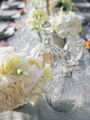 glass bowls with glass stoppers interspersed among flower arrangements