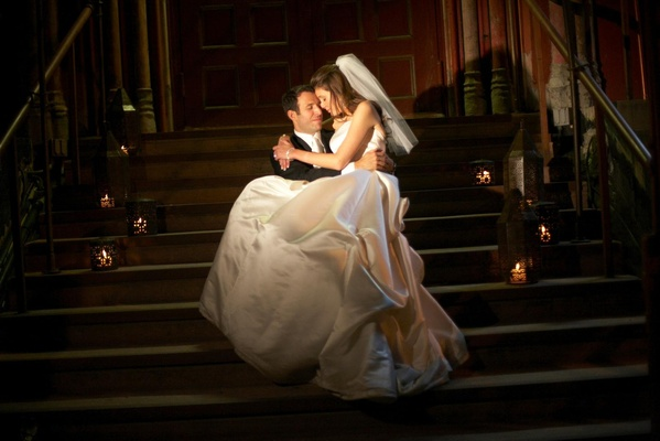 groom holds bride wearing ball gown on staircase