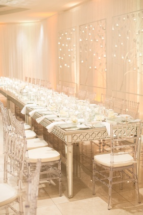 Clear chairs around mirror dinner table at modern reception