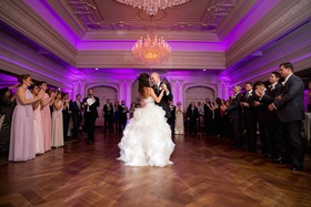 Bride in a strapless Lazaro dress with beaded belt, ruffled skirt dances with groom at Park Savoy