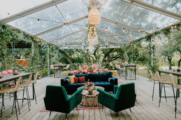 wedding reception clear tent rattan pendant chandelier velvet lounge furniture bar stools lights