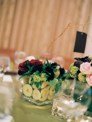 Small wedding centerpiece in square glass vase with green apples