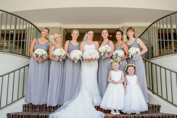 Bridesmaids in V-neck silver gowns with bouquets white flowers dusty miller flower girls crowns