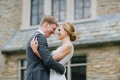 blonde bride with low chignon bun hugs groom in grey suit