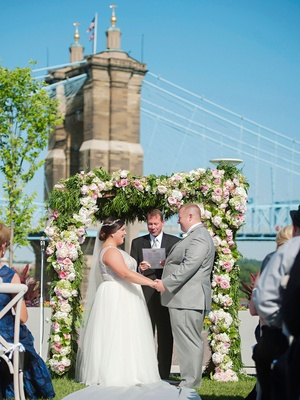 Wedding ceremony with bridge in background flower greenery arch bride in sleeveless gown grey suit