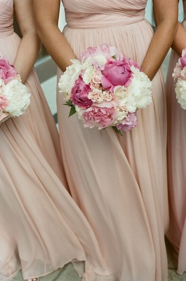 Bridesmaids in pale dresses holding peony flowers