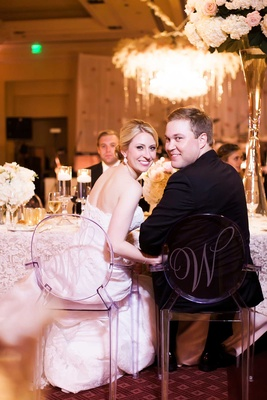 couple turn around reception chairs posing W initials ghost clear reception dallas texas smiling