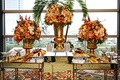 Wedding appetizer tables with mirrored panels and golden urns with yellow, orange, and pink flowers