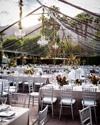 Wedding reception outdoor silver chairs fall color centerpieces chandeliers tent made out of lights
