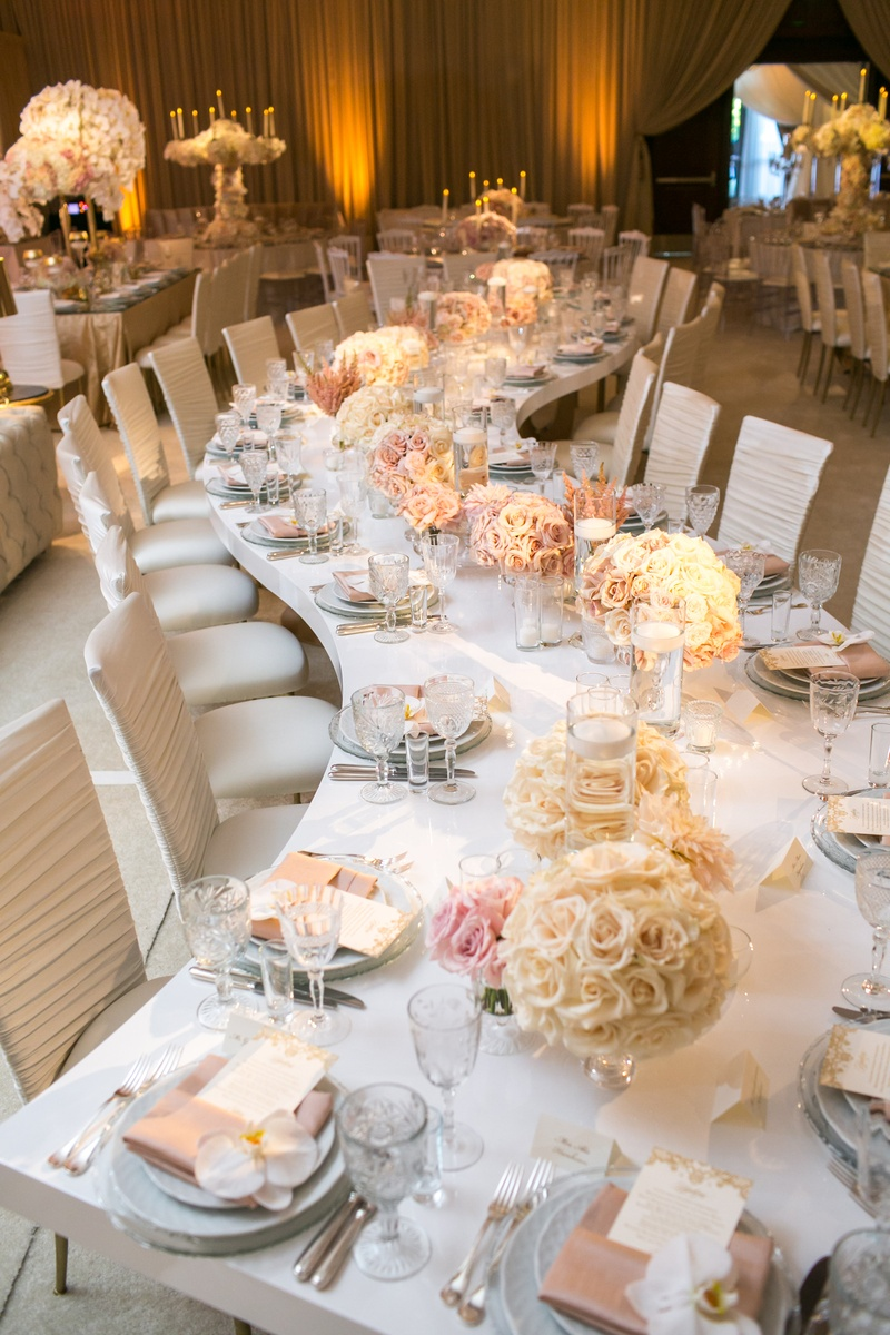 a long serpentine table with round white rose arrangements along the center