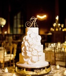 four-tiered cake with fondant frosting and oversized white flower trimmed in gold, initial topper
