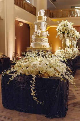 six-tier cake with painted gold leaf and handmade sugar flowers, crystals on stand, floral display