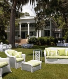 outdoor lounge area with white wicker furniture and green pillows and cushions