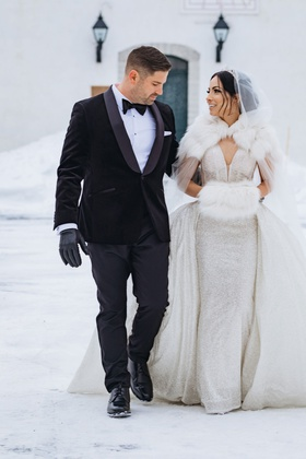 groom in tuxedo bow tie and black gloves bride in sparkle dress overskirt fur hand muff cape hood