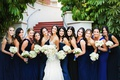 bride with bridesmaids in mismatched bright blue wedding dresses white rose bouquets