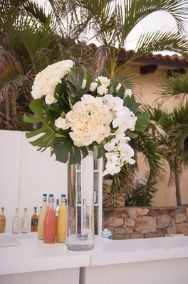 wedding bar with display of split leaves, ivory roses, white orchids
