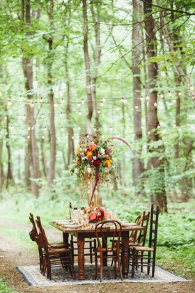 Wedding reception country table surrounded by mismatched wooden chairs on an oriental rug