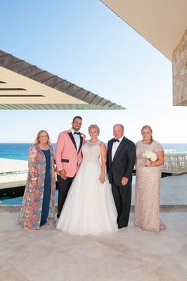 bride in mark zunino, groom in salmon suit jacket, family of the bride portrait