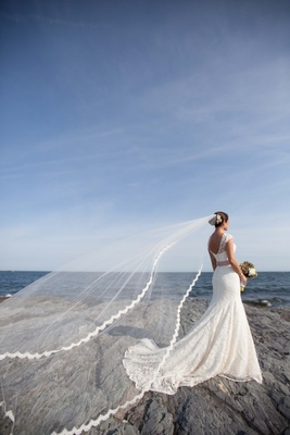Bride's Lela Rose veil is picked up by the wind in Newport, RI