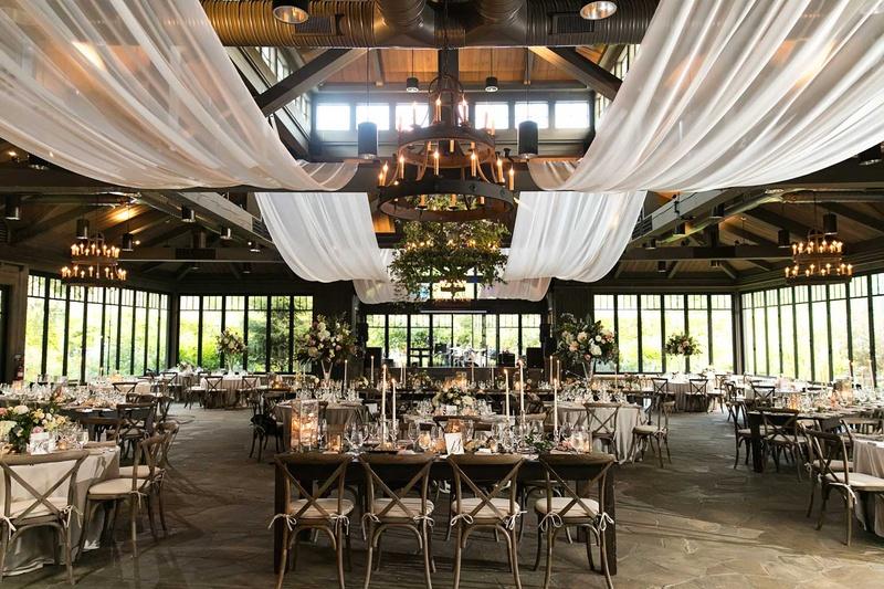 wedding reception in barn drapery rafters beams chandelier greenery wood table chairs