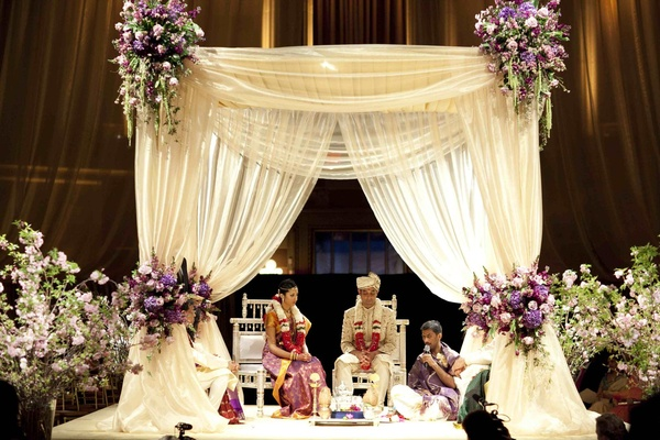 Indian Hindu wedding ceremony with a white mandap and purple flowers