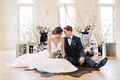 styled shoot wedding inspiration, bride in hayley paige, groom in suit, sitting on cow-skin rug