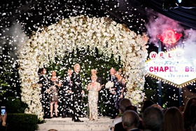 couple at wedding ceremony vow renewal white flower chuppah chapel of the bells las vegas sign elope