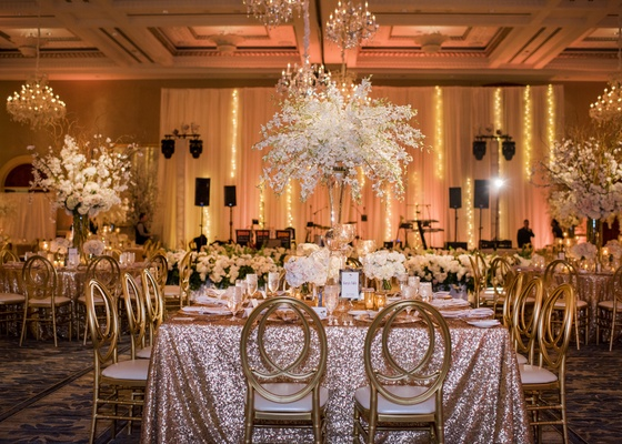 wedding reception with rose gold linens, gold chairs, centerpiece with dendrobium orchids