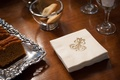 Cocktail napkin with gold J&J monogram at wedding