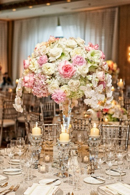 Wedding reception table with roses, hydrangeas, orchids in white, pink, & green, crystal candlehold