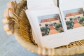 Basket filled with wedding ceremony programs with drawing of The Inn at Rancho Santa Fe on front