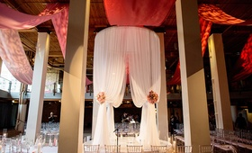 tall white fabric chuppah with clear chairs surrounding