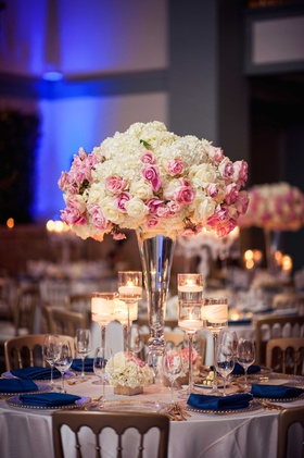 White hydrangea pink rose flower arrangement floating candles navy blue cobalt napkins gold chairs