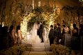 Bride and groom beneath flower arch at ballroom ceremony