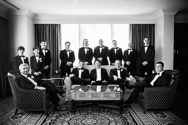 Black and white photo of groom and groomsmen in hotel room in Chicago before wedding