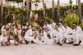 boho-chic wedding party in crouched rap pose