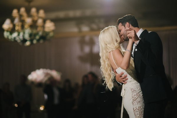 Groom in black tuxedo kisses bride in Galia Lahav gown with lace panels during first dance