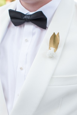 Gold leaf and quartz wedding boutonniere on ivory suit jacket black bow tie