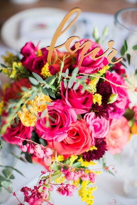 colorful floral arrangement with pink red yellow flowers and greenery gold laser cut table number