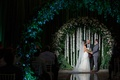 wedding ceremony bride and groom flower circle arch cascading white flowers greenery lighting