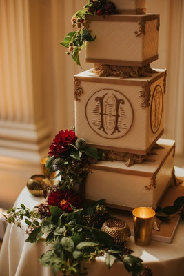 wedding cake square rectangular layers with gold monogram greenery red burgundy flowers candlelight