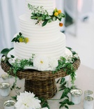 three tier white wedding cake greenery wicker flowers candles leaves oceanside california wedding