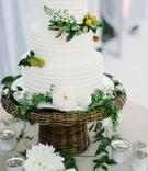 three tier white wedding cake greenery wicker flowers candles leaves oceanside california wedding