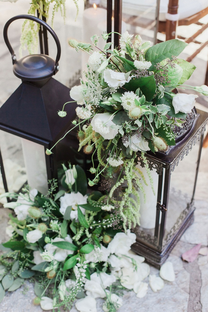 black lanterns at front of ceremony with white flowers and greenery